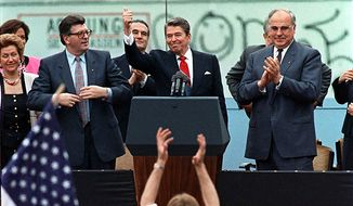 """A spectator jumps up as then-President Ronald Reagan gives a thumbs-up sign after his speech in front of the Brandenburg Gate in West Berlin, where he said """"Mr. Gorbachev, tear down this wall."""" (Associated Press) ** FILE **"""