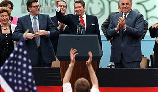 "A spectator jumps up as President Reagan gives a thumbs up sign after his speech in front of the Brandenburg Gate in West Berlin, where he said ""Mr. Gorbachev, tear down this wall."" (Associated Press)"