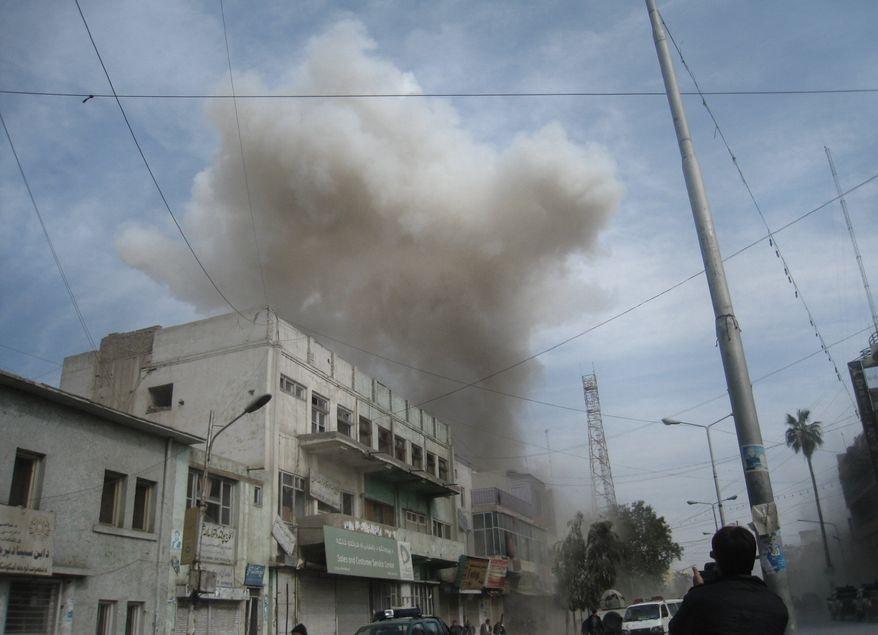 Smoke rises from the Kabul Bank branch in Jalalabad, Afghanistan, east of Kabul, on Saturday, Feb. 19, 2011, after gunmen wearing explosives vests stormed the bank as government employees were waiting to be paid. Authorities said 38 people were killed. (AP Photo/Shir Shah Hamdard)