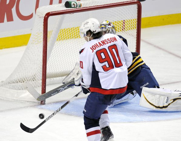 Washington Capitals center Marcus Johansson (left) shoots and scores on Buffalo Sabres goalie Ryan Miller during the third period of the Capitals' 2-1 win Sunday in Buffalo. (Associated Press)