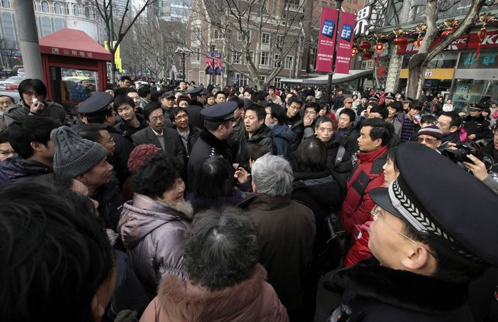 """Police officers urge people to leave from in front of a cinema that was a planned protest site in Shanghai, China, on Sunday, Feb. 20, 2011. Jittery Chinese authorities staged a show of force to squelch a mysterious online call for a """"Jasmine Revolution,"""" apparently modeled after pro-democracy demonstrations sweeping the Middle East. (AP Photo/Eugene Hoshiko)"""
