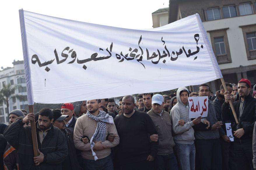 """Protesters hold a banner reading """"For a government chosen by the people"""" during a demonstration on Sunday in Casablanca, Morocco. Thousands of people marched in cities across Morocco, demanding a new constitution to bring more democracy in the North African kingdom amid the wave of Arab world upheaval. (Associated Press)"""