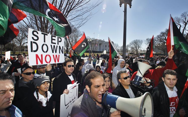 Hossam Mansour (center) joins protesters waving Libyan flags in front of the White House in Washington on Saturday, Feb. 19, 2011, to call for the ouster of Libyan leader Moammar Gadhafi. (AP Photo/Manuel Balce Ceneta)