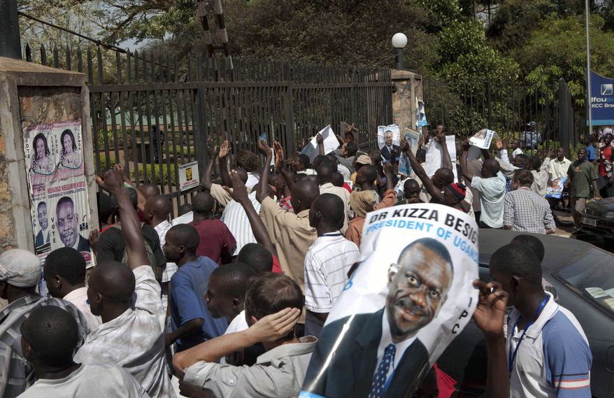 A supporter of Ugandan opposition leader Kizza Besigye holds a poster with his likeness as demonstrators stage a protest in Kampala, Uganda, the nation's capital, on Sunday, Feb. 20, 2011. The Electoral Commission on Sunday said President Yoweri Museveni had won 68 percent of votes in Friday's poll, allowing him to extend his 25-year hold on power, but Mr. Besigye alleged fraud and vowed to reject the results. (AP Photo/Michele Sibiloni)