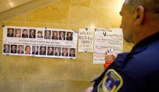 Police officer Greg Friberg of Milwaukee looks a poster at the Capitol in Madison, Wis. Opponents of a bill to limit collective-bargaining rights protested for the sixth day. (Associated Press)