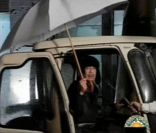 Libyan leader Moammar Gadhafi is shown in this video image broadcast on Libyan state television early Tuesday. Gadhafi appeared for less than a minute on state television and made brief remarks to say he was in Tripoli and to deny rumors he had to fled to Venezuela amid the unrest sweeping his country. (Associated Press)