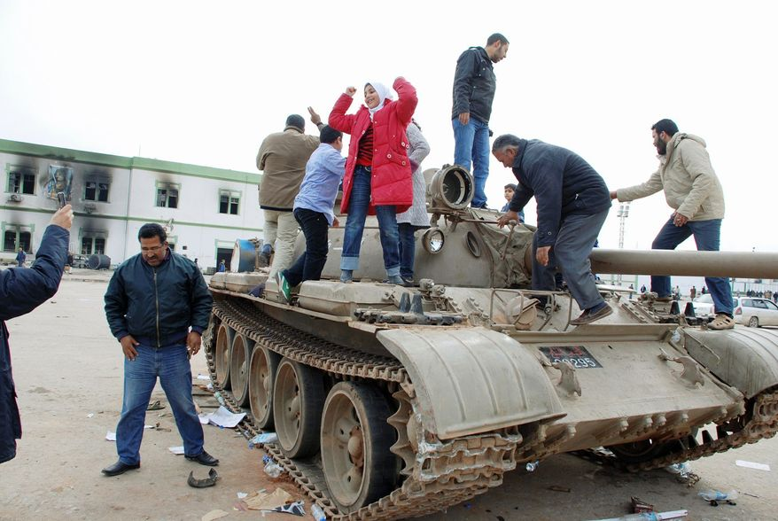 TAKING A TANK: Protesters celebrate on a tank inside a security-forces compound in Benghazi, Libya, on Monday. Demonstrators rallied in the streets of Benghazi as they claimed control of the country's second-largest city. (Associated Press)