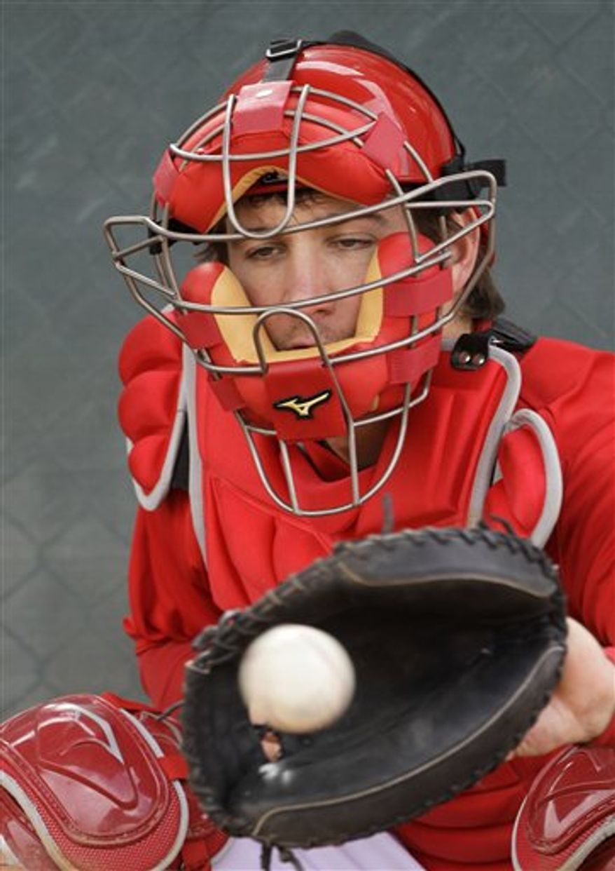Los Angeles Angels catcher Jeff Mathis catches a bullpen session during baseball spring training, Saturday, Feb. 19, 2011, in Tempe, Ariz. (AP Photo/Mark Duncan)