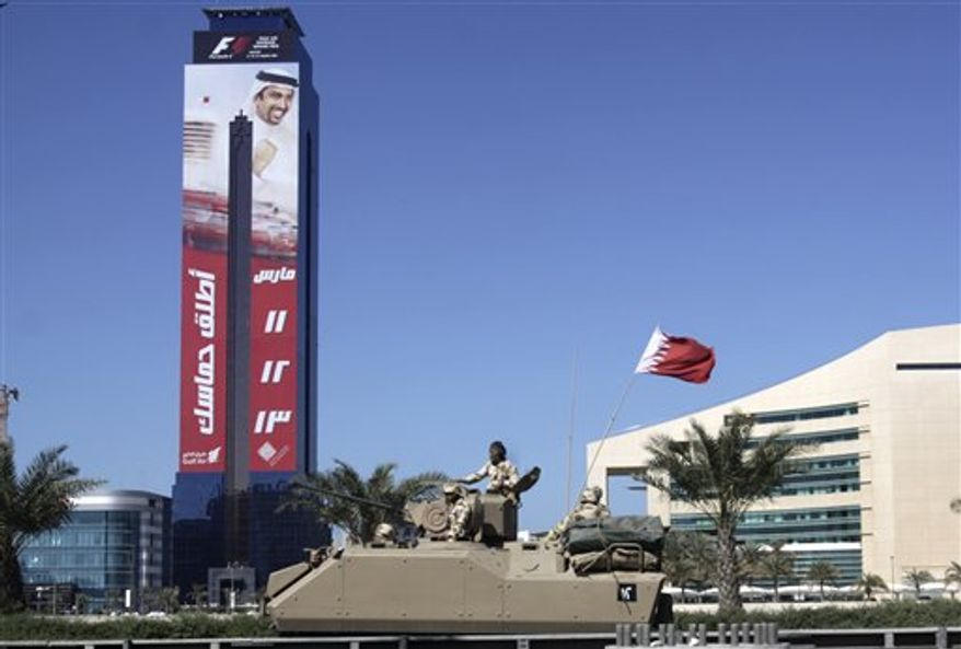 "FILE - In this Saturday, Feb. 19, 2011 file photo, a Bahraini military armored personnel carrier (APC) pulls out from the Pearl roundabout in Manama, Bahrain, past a banner advertising the Formula One race seen on a building behind. The season-opening Formula One race in Bahrain was called off Monday due to the anti-government protests in the Gulf kingdom. Writing on banner in arabic reads ""Release your enthusiasm. 11-12-13 March"". (AP Photo/Hasan Jamali, File)"
