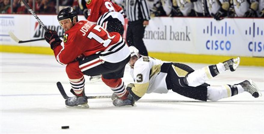Chicago Blackhawks' Ryan Johnson (17) and the Pittsburgh Penguins' Alex Goligoski (3) look for the puck during the third period of an NHL Hockey game, Sunday, Feb. 20, 2011, in Chicago. (AP Photo/Jim Prisching)