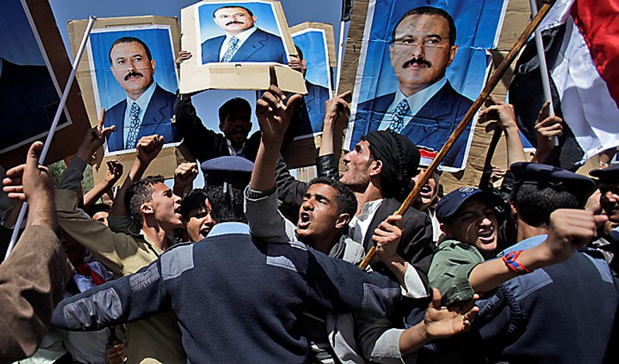Yemeni policemen push back government supporters raising posters showing President Ali Abdullah Saleh as they shout at anti-government demonstrators (not pictured) in Sanaa, Yemen, on Sunday, Feb. 20, 2011. Some 3,000 students protesting at Sanaa University in the Yemeni capital sought to oust longtime President Ali Abdullah Saleh, a key U.S. ally in the fight against al Qaeda, and have been inspired by uprisings in Egypt and Tunisia. (AP Photo/Muhammed Muheisen)