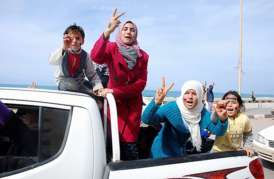 Residents riding in the back of a vehicle celebrate and display the victory sign in Benghazi, Libya, on Monday, Feb. 21, 2011. Libyan protesters celebrated in the streets of Benghazi on Monday, claiming control of the country's second-largest city after bloody fighting, and anti-government unrest spread to the capital, with clashes in Tripoli's main square for the first time. (AP Photo/Alaguri)