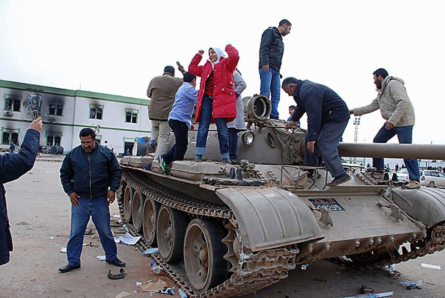Residents stand on a tank inside a security forces compound in Benghazi, Libya, on Monday, Feb. 21, 2011. Libyan protesters celebrated in the streets of Benghazi on Monday, claiming control of the country's second-largest city after bloody fighting, and anti-government unrest spread to the capital, with clashes in Tripoli's main square for the first time. (AP Photo/Alaguri)