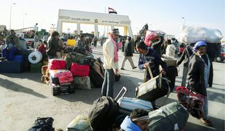 EXIT STRATEGY: Egyptians, seeking to flee Libya through the Salloum land port gate (rear), wait with their luggage Tuesday. They were among thousands fleeing the violence. (Associated Press)