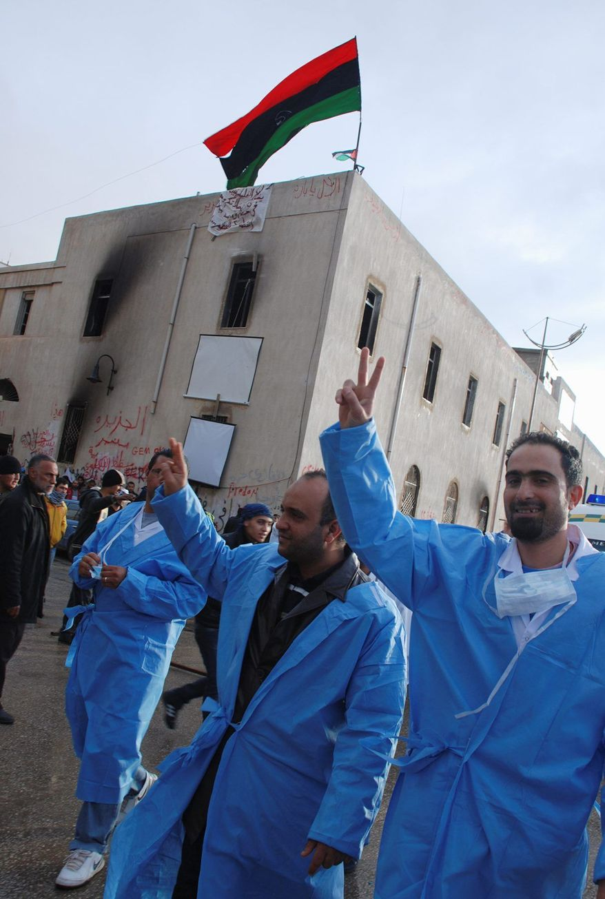 With a Libyan flag from the pre-Gadhafi era flying on the building, medical volunteers march in front of Benghazi court Tuesday. Libyan leader Moammar Gadhafi continued to reject calls for his resignation, even as three more Libyan ambassadors resigned in protest. (Associated Press)