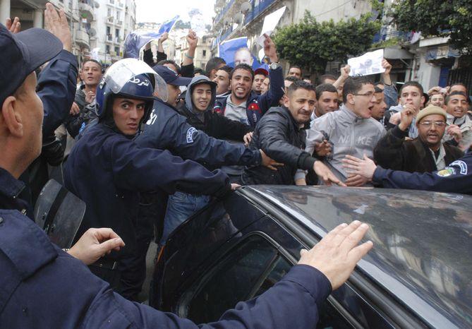 Riot police officers control pro-government demonstrators, some holding portraits of Algerian President Abdelaziz Bouteflika, in Algiers, Saturday, Feb. 19, 2011. (AP Photo/Sidali Djarboub)