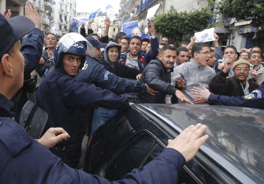 Riot police officers control pro-government demonstrators, some holding portraits of Algerian President Abdelaziz Bouteflika, in Algiers, Saturday, Feb. 19, 2011. (AP Photo/Sidali Djarboub)
