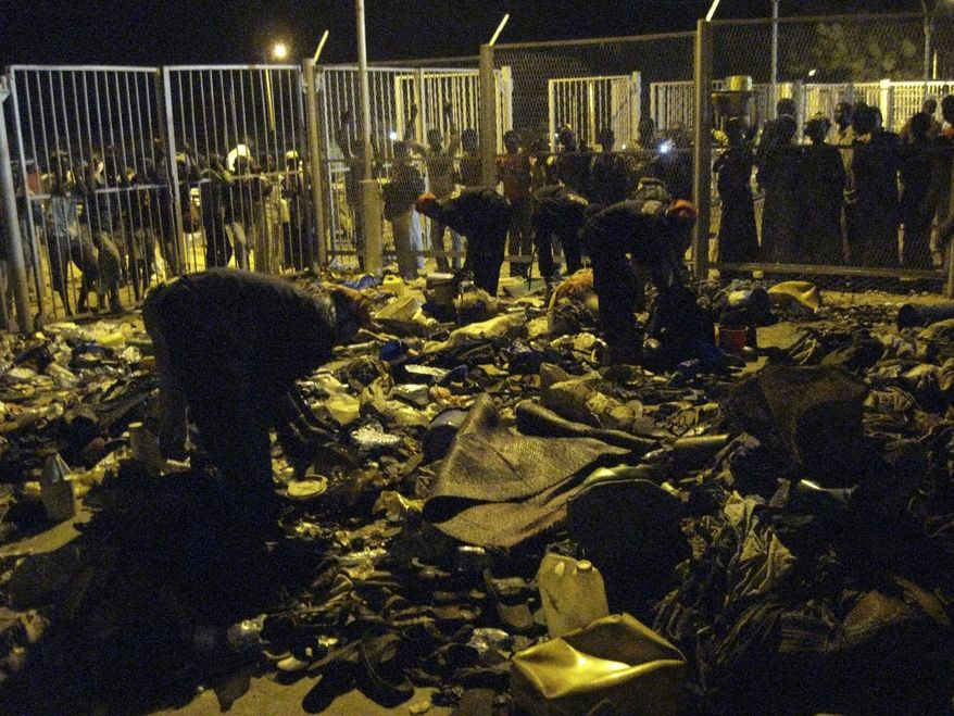 People look on as security guards clean up personal belongings and debris following a deadly stampede at Modibo Keita Stadium in Bamako, Mali, Monday, Feb. 21, 2011. At least 36 people were killed in the stampede Monday when a crowd surged against a metal barrier after a Muslim ceremony, Mali's minister of interior security and civil protection said. (AP Photo/Martin Vogl)