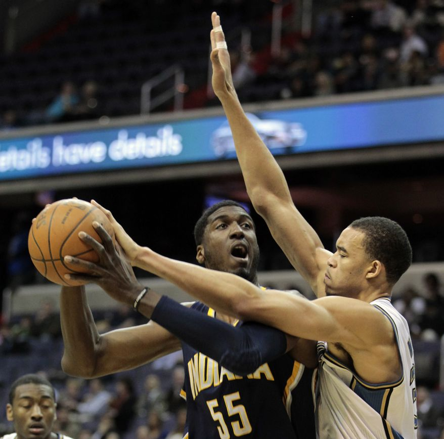 Washington Wizards center JaVale McGee, right, reaches for the ball in the hands of Indiana Pacers center Rob Hibbert in the first half of an NBA basketball game, Tuesday, Feb. 22, 2011, in Washington. (AP Photo/Alex Brandon)