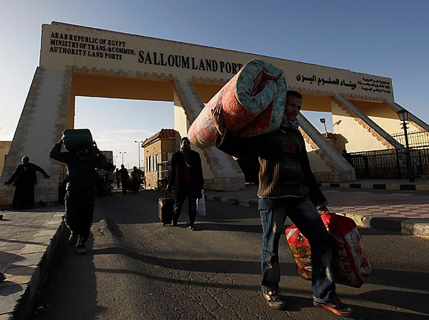 Egyptians who fled from Libya through the Salloum land port gate carry their belongings at the Egyptian-Libyan border, in Salloum, Egypt, Tuesday, Feb. 22, 2011. An estimated 5,000 Egyptians have returned home from Libya by land, and about 10,000 more are waiting to cross the Libya-Egypt border, an Egyptian security official said Tuesday. (AP Photo/Hussein Malla)