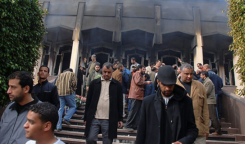 Residents are seen outside an unidentified burned building in Benghazi, Libya, on Monday, Feb. 21, 2011. Libyan protesters celebrated in the streets of Benghazi on Monday, claiming control of the country's second largest city after bloody fighting, and anti-government unrest spread to the capital with clashes in Tripoli's main square for the first time. (AP Photo/Alaguri)