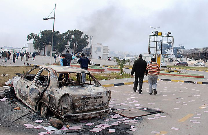 Residents are seen walking past a burned-out vehicle in Benghazi, Libya, on Monday, Feb. 21, 2011. Libyan protesters celebrated in the streets of Benghazi on Monday, claiming control of the country's second largest city after bloody fighting, and anti-government unrest spread to the capital with clashes in Tripoli's main square for the first time. (AP Photo/Alaguri)