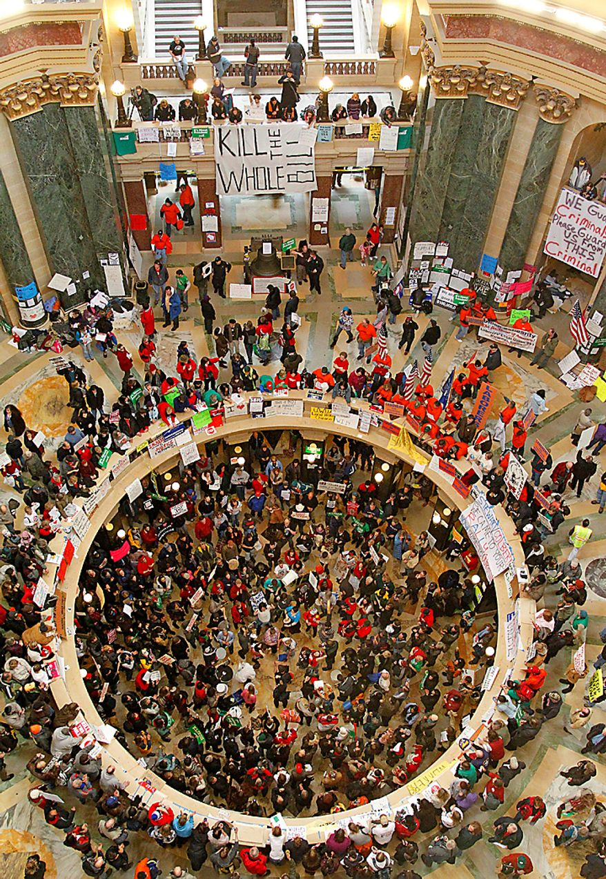 Protesters bang drums and chant inside the state Capitol on Tuesday, Feb. 22, 2011, in Madison, Wis. Opponents to Gov. Scott Walker's bill to eliminate collective bargaining rights for many state workers are taking part in their eighth day of protests. (AP Photo/Jeffrey Phelps)