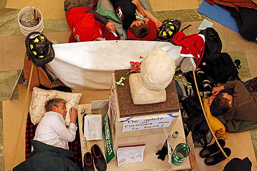 Protesters sleep inside the state Capitol on Tuesday, Feb. 22, 2011, in Madison, Wis. Opponents of Gov. Scott Walker's bill to eliminate collective bargaining rights for many state workers are taking part in their eighth day of protests. (AP Photo/Jeffrey Phelps)