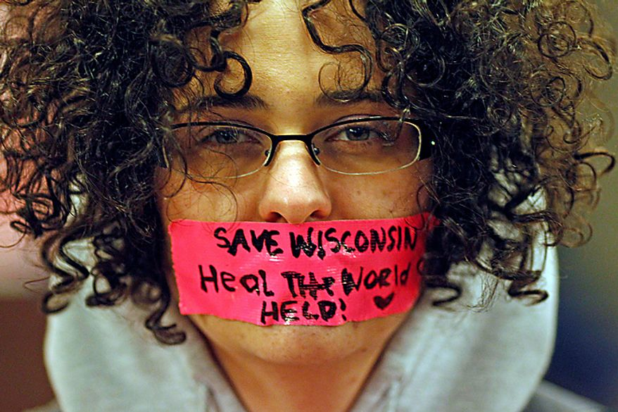 Kathryn Schulze wears a message written on tape over her mouth inside the Wisconsin Capitol on Monday, Feb. 21, 2011, in Madison, Wis. Opponents of Gov. Scott Walker's bill to eliminate collective bargaining rights for many state workers are taking part on Tuesday in their eighth day of protests. (AP Photo/Jeffrey Phelps)
