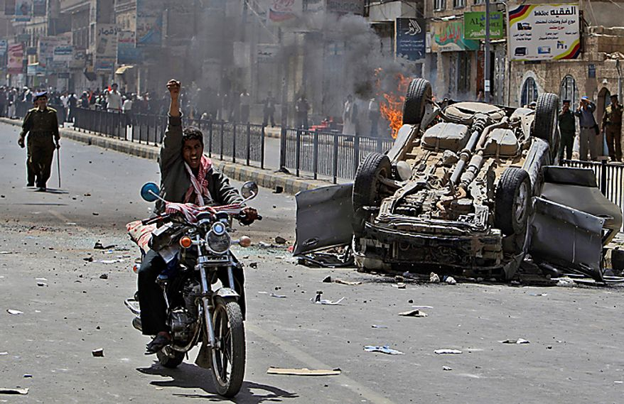 A Yemeni anti-government demonstrator rides his bike past a burning vehicle belonging to supporters of President Ali Abdullah Saleh during clashes in Sanaa, Yemen, Tuesday, Feb. 22, 2011. Yemen's embattled leader rejects demands that he step down, calling demonstrations against his regime unacceptable acts of provocation and offers to begin a dialogue with protesters. (AP Photo/Muhammed Muheisen)