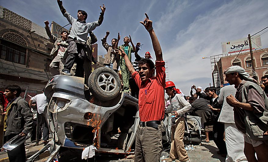 Yemeni anti-government demonstrators shout at supporters of President Ali Abdullah Saleh, not pictured, as they gather a top and around a destroyed vehicle belonging to the supporters, during clashes in Sanaa, Yemen, Tuesday, Feb. 22, 2011. Yemen's embattled leader rejects demands that he step down, calling demonstrations against his regime unacceptable acts of provocation and offers to begin a dialogue with protesters. (AP Photo/Muhammed Muheisen)