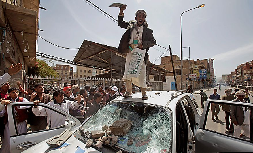 A Yemeni anti-government demonstrator stands on top of a destroyed vehicle belongs to supporters of President Ali Abdullah Saleh during clashes in Sanaa, Yemen, Tuesday, Feb. 22, 2011. Yemen's embattled leader rejects demands that he step down, calling demonstrations against his regime unacceptable acts of provocation and offers to begin a dialogue with protesters. (AP Photo/Muhammed Muheisen)
