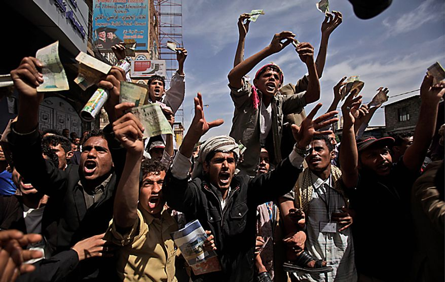 Yemeni anti-government demonstrators display their local currency during a demonstration demanding the resignation of President Ali Abdullah Saleh, in Sanaa, Yemen, Tuesday, Feb. 22, 2011. Yemen's embattled leader rejects demands that he step down, calling demonstrations against his regime unacceptable acts of provocation and offers to begin a dialogue with protesters. (AP Photo/Muhammed Muheisen)
