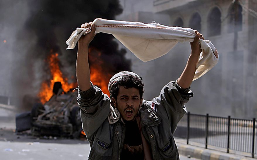A Yemeni anti-government demonstrator reacts after other demonstrators set on fire a vehicle belonging to supporters of President Ali Abdullah Saleh during clashes in Sanaa, Yemen, Tuesday, Feb. 22, 2011. Yemen's embattled leader rejects demands that he step down, calling demonstrations against his regime unacceptable acts of provocation and offers to begin a dialogue with protesters. (AP Photo/Muhammed Muheisen)