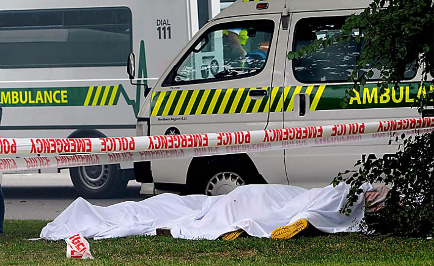 Bodies are covered after an earthquake rocked Christchurch, New Zealand, Tuesday, Feb. 22, 2011. The 6.3-magnitude quake hit at the height of a busy workday, toppling tall buildings and churches, crushing buses and killing dozens people in one of the country's worst natural disasters. (AP Photo/NZPA, David Wethey)