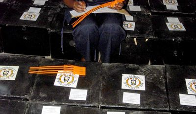 A member of the Uganda Electoral Commission checks ballot boxes in Kampala. An African mission led by Zimbabwean Ambassador Simbi Veke Mubako was sent to observe the presidential election Friday. (Associated Press)