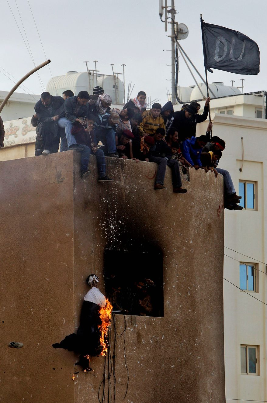 In Tobruk, Libya, protesters stand atop a damaged police station Wednesday as they burn an effigy of Gadhafi during a demonstration against his regime. (Associated Press)
