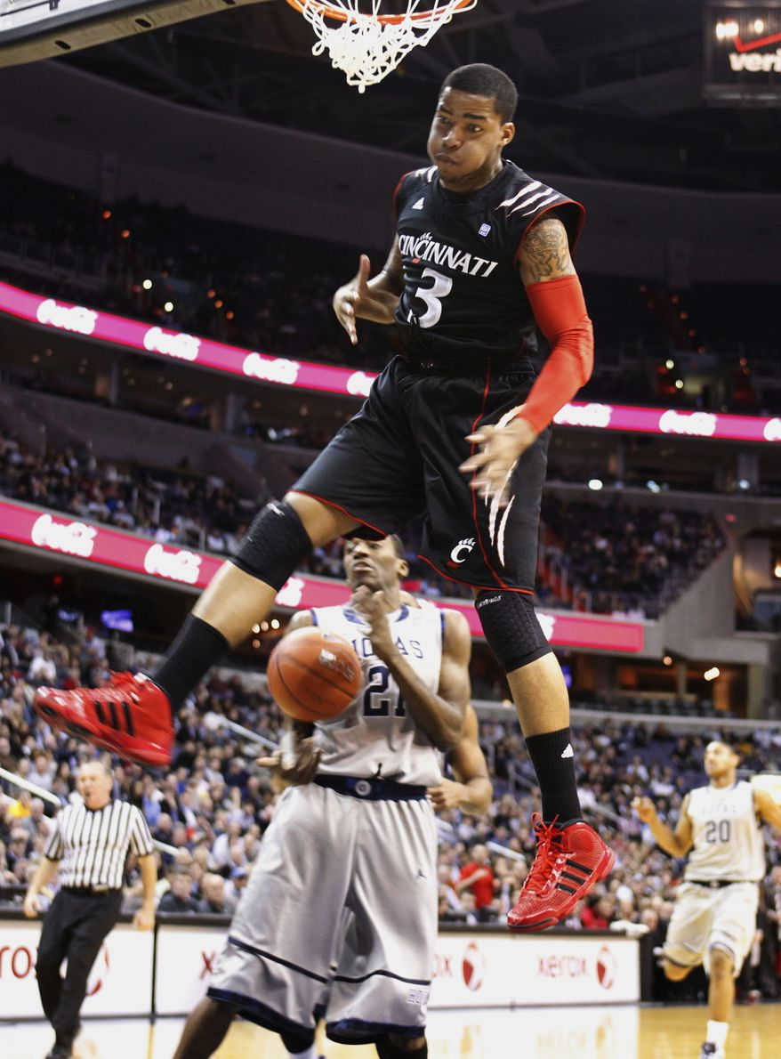 Cincinnati's Dion Dixon (3) scores as Georgetown's Jason Clark (21) looks on during the first half of an NCAA college basketball game in Washington, Wednesday, Feb. 23, 2011. (AP Photo/Manuel Balce Ceneta)