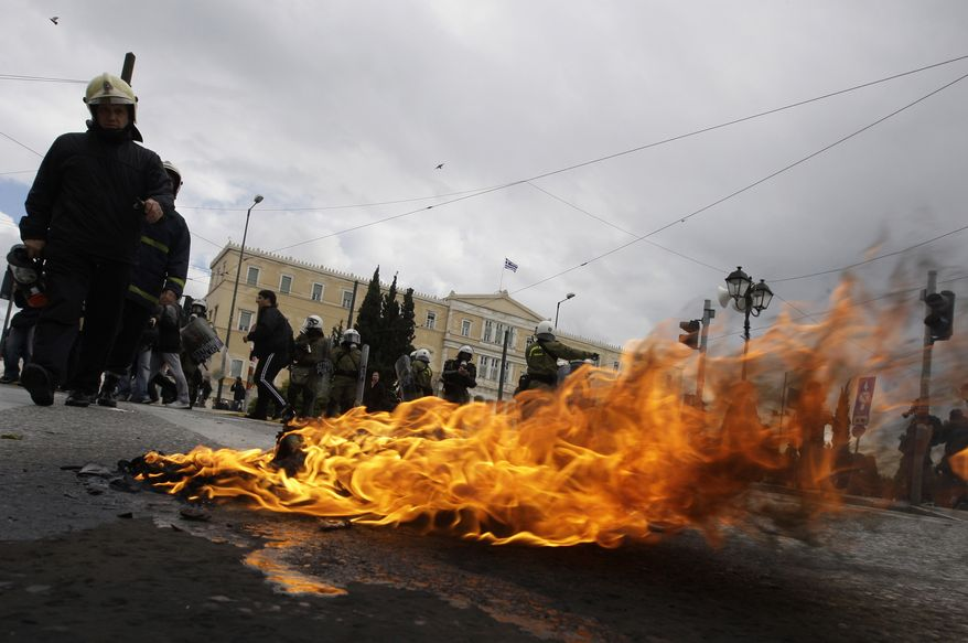 A Molotov cocktail thrown by protesters burns in front of the Greek parliament on Syntagma Square in central Athens on Wednesday, Feb. 23, 2011. Scores of youths hurled rocks and gasoline bombs at riot police after clashes broke out during a mass rally taking place as part of a general strike. (AP Photo/Petros Giannakouris)