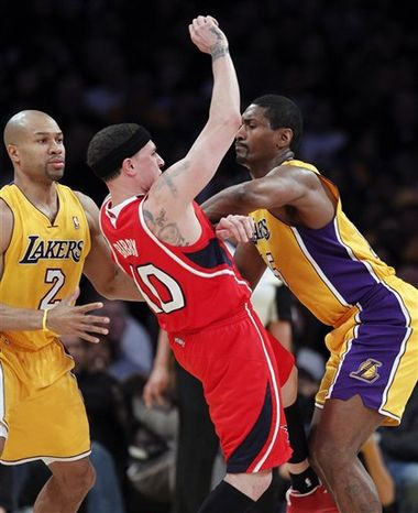 Los Angeles Lakers forward Ron Artest, right, give Atlanta Hawks guard Mike Bibby (10) a forearm block for a foul as lakers guard Derek Fisher (2) watches during the first half of an NBA basketball game, Tuesday, Feb. 22, 2011, in Los Angeles. (AP Photo/Alex Gallardo)