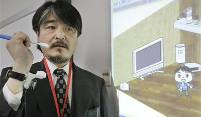 In this Tuesday, Feb. 22, 2011 photo, Nippon Telegraph and Telegram Corp. Communications Science Laboratories staff imitates to brush his teeth during a demonstration of a wearable sensor attached to a wristwatch-like device during the NTT Research and Development Forum in Tokyo. Japan's top telecom company NTT says using this technology, what an elderly person is doing during each hour of the day can be shown on a chart. (AP Photo/Koji Sasahara)