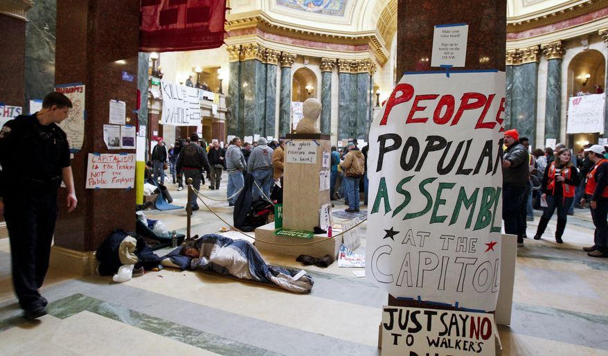 A police officer walks by someone sleeping at the state Capitol in Madison, Wis., Wednesday, Feb. 23, 2011, on the ninth day of protests against Gov. Scott Walker's plan to strip public sector workers of nearly all of their bargaining rights. (AP Photo/Andy Manis)