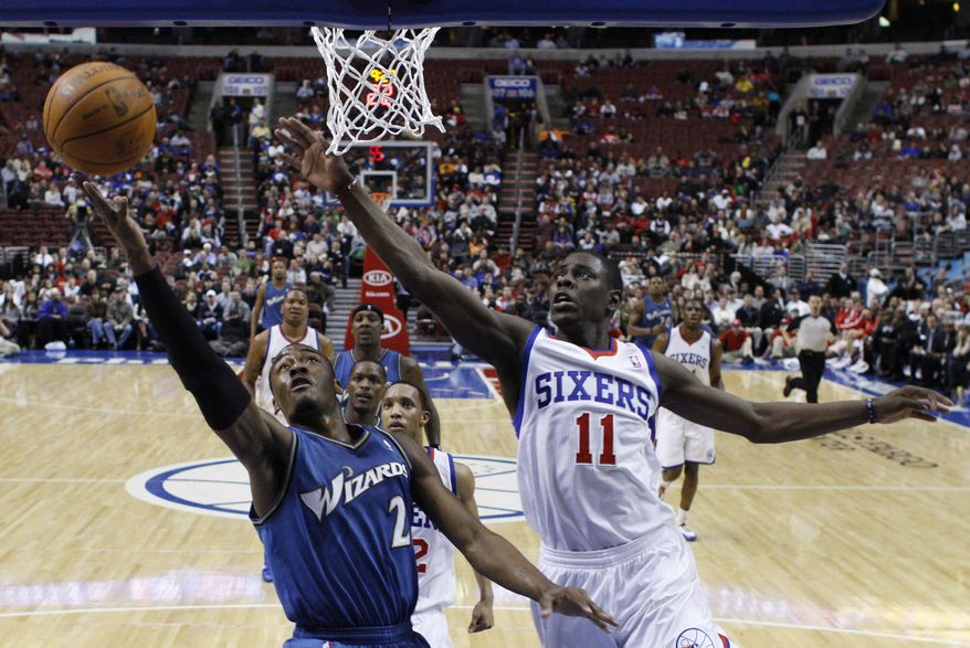 In this file photo, Washington Wizards' John Wall (2) drives to the basket as Philadelphia 76ers' Jrue Holiday (11) defends in the first half of an NBA basketball game, Wednesday, Feb. 23, 2011, in Philadelphia. (AP Photo/Matt Slocum)