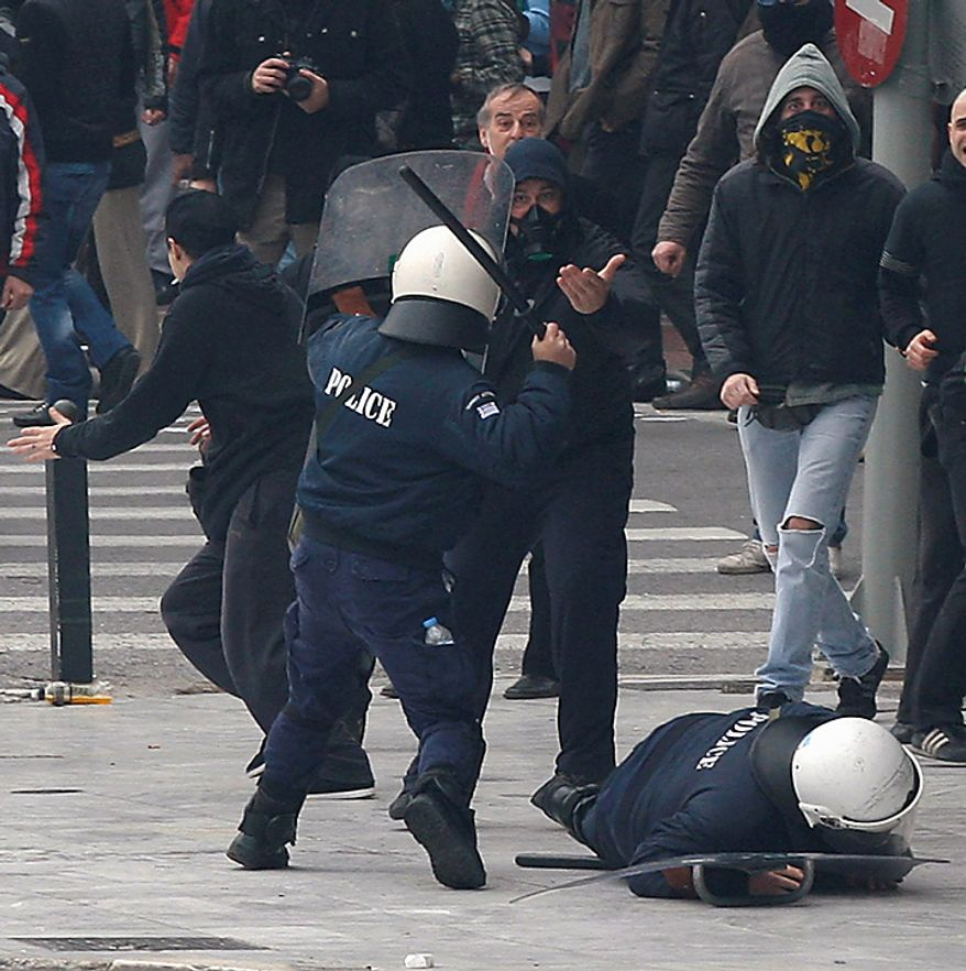 A riot policeman clashes with protesters as his colleague falls down during clashes in Athens on Wednesday, Feb. 23, 2011. Scores of youths hurled rocks and petrol bombs at police after clashes broke out during a mass rally taking place as part of a general strike. (AP Photo/Thanassis Stavrakis)