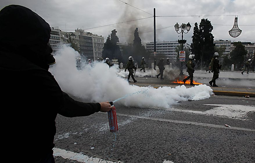 A protester uses a fire extinguisher as riot police pass beside tear gas during clashes in Athens on Wednesday, Feb. 23, 2011. Scores of youths hurled rocks and petrol bombs at riot police after the clashes broke out during a mass rally taking place as part of a general strike. (AP Photo/Kostas Tsironis)