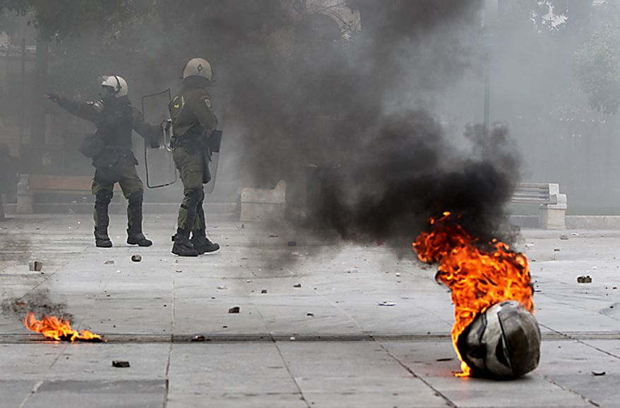 A police helmet is on fire in front of riot policemen in Syntagma Square in central Athens during clashes on Wednesday, Feb. 23, 2011. Scores of youths hurled rocks and gasoline bombs at riot police after the clashes broke out during a mass rally taking place as part of a general strike. (AP Photo/Petros Giannakouris)