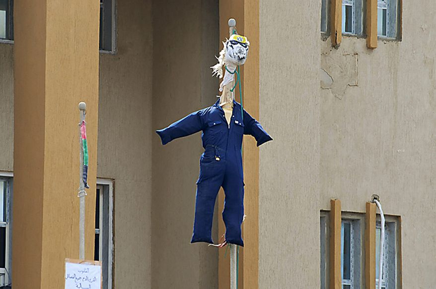 An effigy representing Libyan Leader Moammar Gadhafi, marked with a Star of David on its forehead, hangs from a flagpole in Benghazi, Libya Wednesday, Feb. 23, 2011. Militiamen loyal to Moammar Gadhafi clamped down in Tripoli Wednesday, but cracks in his regime spread elsewhere across the nation, as the protest-fueled rebellion controlling much of eastern Libya claimed new gains closer to the capital. (AP Photo/Alaguri)