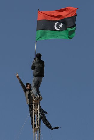 Libyan protesters raise up the old Libyan flag during a demonstration against Libyan Leader Moammar Gadhafi, in Tobruk, Libya, on Wednesday Feb. 23, 2011. Heavy gunfire broke out in Tripoli as forces loyal to Moammar Gadhafi tightened their grip on the Libyan capital while anti-government protesters claimed control of many cities elsewhere and top government officials and diplomats turn against the longtime leader. (AP Photo/Hussein Malla)