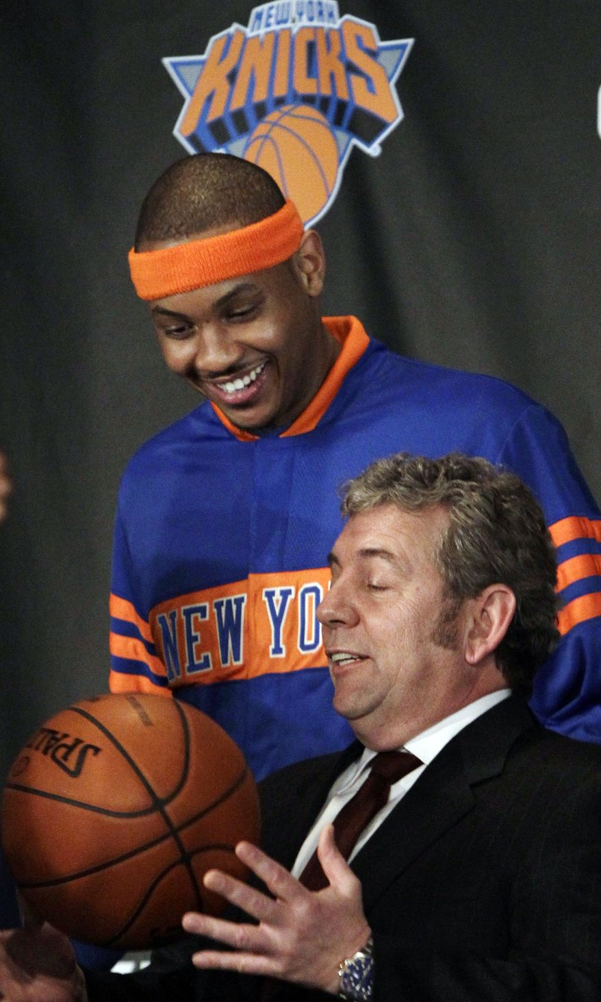 New York Knicks owner James Dolan (bottom) bounces a basketball as he poses for photographs with Carmelo Anthony, the Knicks' newest player, during a Feb. 23 introductory news conference in New York. (Associated Press)