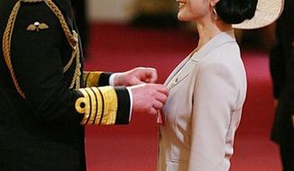 Hollywood actress Catherine Zeta Jones, right,  is invested as a Commander of the British Empire (CBE) by Prince Charles at Buckingham Palace in London, Thursday Feb. 24, 2011. The Welsh-born actress who became an Oscar-winning star will receive the royal honour for her services to the film industry and to charity. (AP Photo / Lewis Whyld, PA) UNITED KINGDOM OUT - NO SALES - NO ARCHIVES